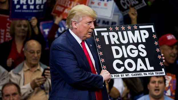 Donald Trump sostiene un cartel que dice