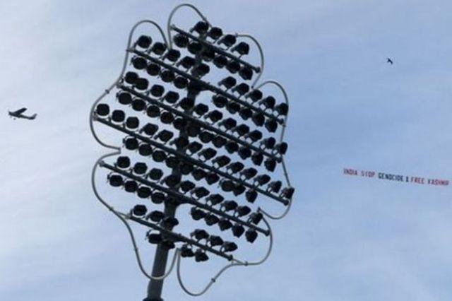 """Samolot lecący nad boiskiem do krykieta z transparentem """"Indie przestańcie ludobójstwa i uwolnić Kaszmir"""""""