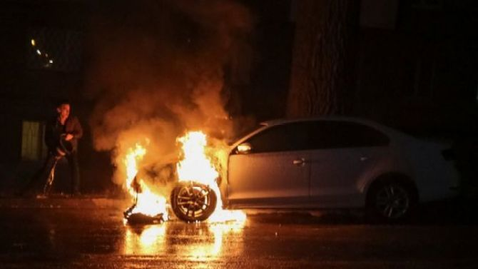 A man extinguishes a burning car of the embassy of Russia after a protest against the seizure by Russian special forces of three Ukrainian naval ships, which Russia blocked from passing through the Kerch Strait into the Sea of Azov in the Black Sea,