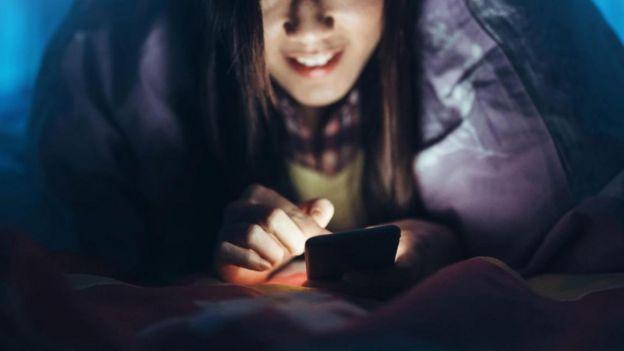 Una joven mira su teléfono en la oscuridad, en su cama
