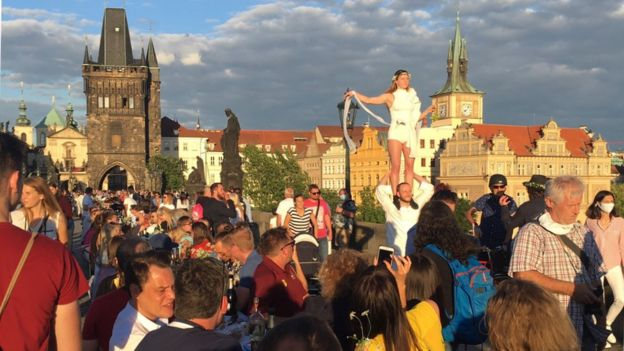 Crowds of people in Prague celebrating the 'end' of the pandemic including a street performer