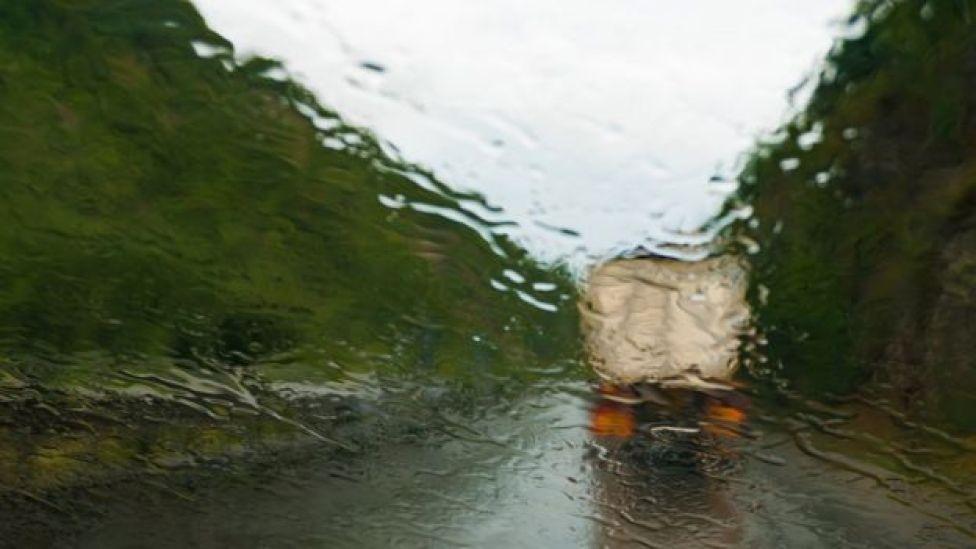 Un camión en la carretera, visto a través del parabrisas de un conductor bajo la lluvia