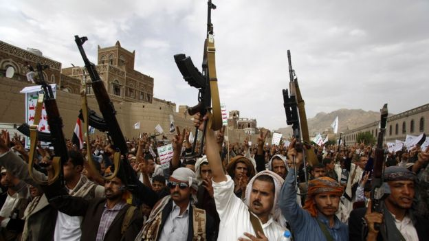 Houthi rebels hold up their weapons as they chant slogans during a rally against Saudi-led air strikes in Sanaa