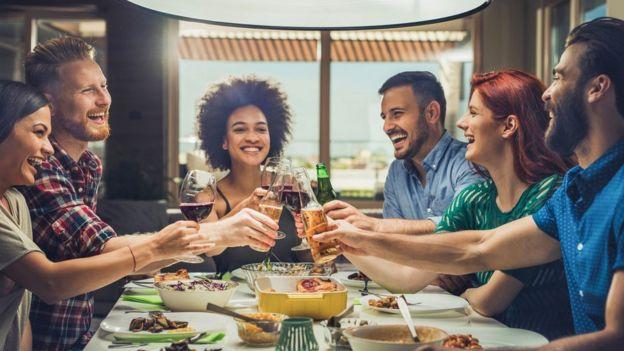 Un grupo de amigos brindando en una mesa.