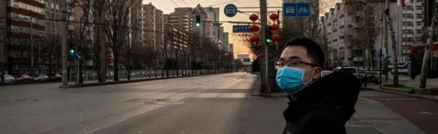 Image shows a Chinese man wearing a protective mask as a preventative measure