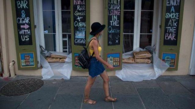 Una mujer pasa frente a tiendas en el Barrio Francés de Nueva Orleans que tienen sacos de arena en preparación para la tormenta tropical Barry.