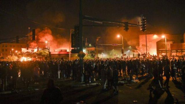 Les manifestants se rassemblent devant le poste de police en feu du 3e district de Minneapolis le 28 mai 2020