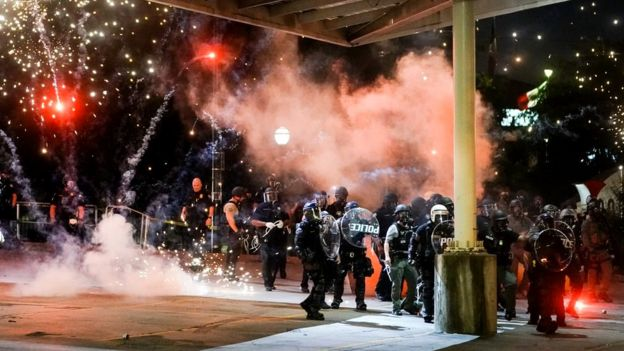A firework explodes near a police line during a protest in Atlanta, Georgia, in response to the police killing of George Floyd, 30 May 2020