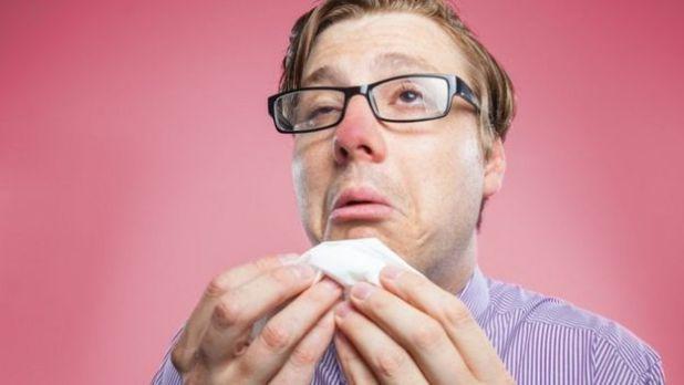 Una persona con cara de resfriado y un papel en la mano