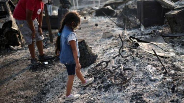 Una niña mira un bici quemada.