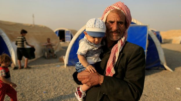 A displaced man carries his nephew as he stands beside tents upon his arrival at al-Khazar camp, east of Mosul, (26 October 2016)