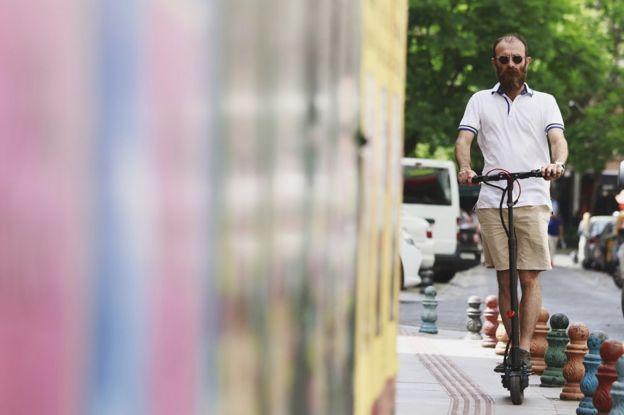 Homem pilotando um patinete elétrico em uma calçada