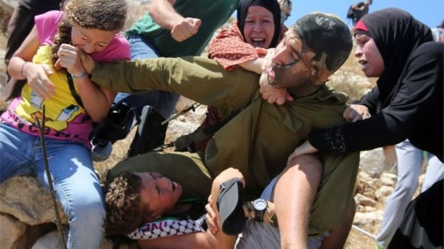 Ahed Tamimi (left) bites an Israeli soldier trying to detain her brother (28/08/15)