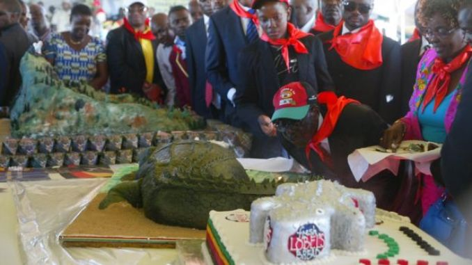 Zimbabwe's President Robert Mugabe blows candles on a crocodile shaped cake during a rally marking his 88th birthday in Mutare on February 25, 2012.