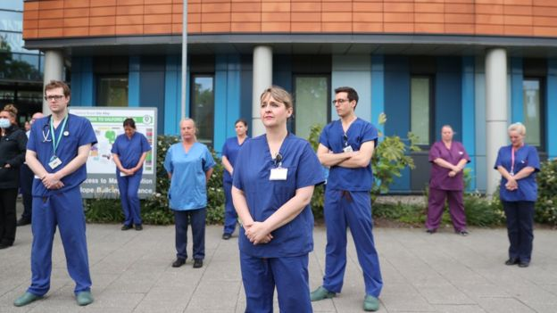 """Staff stand outside Salford Royal Hospital in Manchester during a minute""""s silence to pay tribute to the NHS staff and key workers who have died during the coronavirus outbreak."""