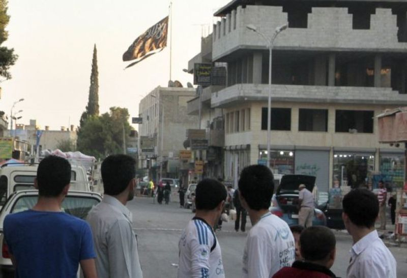 """A group of men look at a large black jihadist flag with Islamic writing on it proclaiming, """"There is no God but God, and Mohammed is the prophet of God""""."""