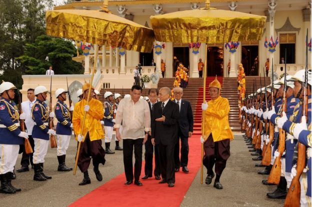 Philippines President Rodrigo Duterte (centre L) and Cambodian King Norodom Sihamoni (centre R) walk past honour guards during a meeting at the Royal Palace in Phnom Penh on December 14, 2016.