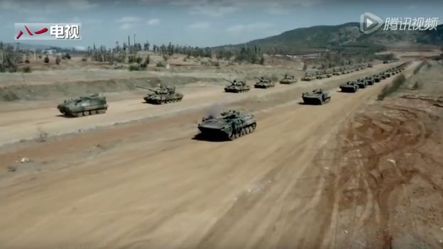 Two lines of tanks driving towards the camera
