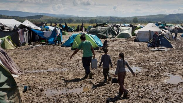 Migrants walk through mud at the migrant camp in Idomeni, Greece, Sunday 22 May 2016.