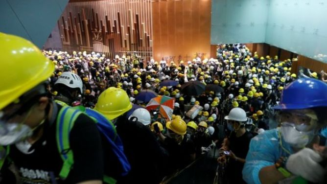 hundreds of people swarm the lobby of a legislative building, their yellow hard harts contrasting the warm colours of the wooden relief carving against one wall