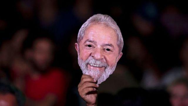 Manifestante levanta máscara com a imagem do rosto do ex-presidente Lula