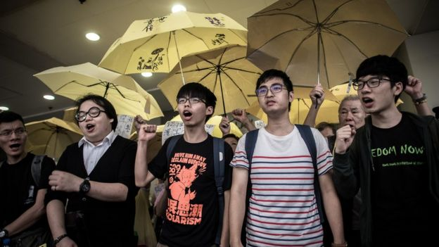 Student protesters Joshua Wong (C), Alex Show (2nd L) and Nathan Law (R) shout slogans outside a court of justice in Hong Kong on September 2, 2015