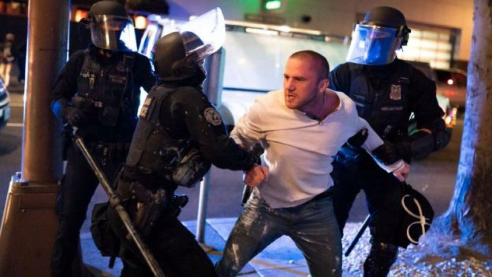 Police restraining a man during the Portland clashes