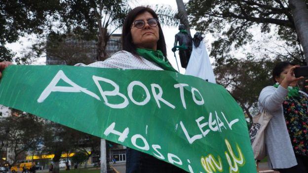 """Mujer con una banderola que dice """"aborto legal""""."""