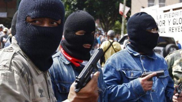 Três homens encapuzados com armas
