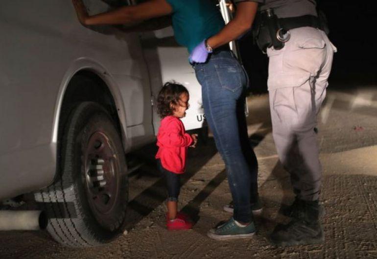 Un agente de la Patrulla Fronteriza cachea a la madre de la pequeña.