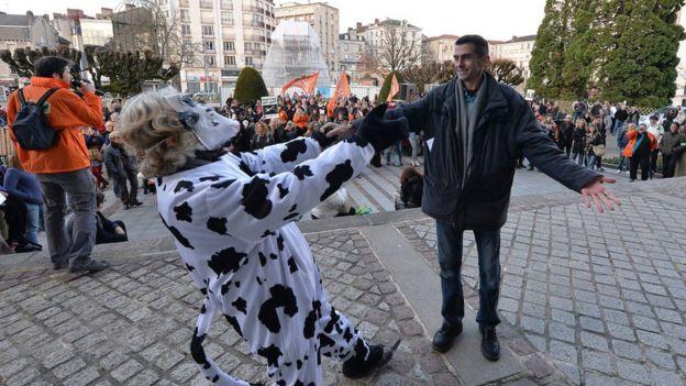 Mauricio García abraza a un activista disfrazado de vaca.