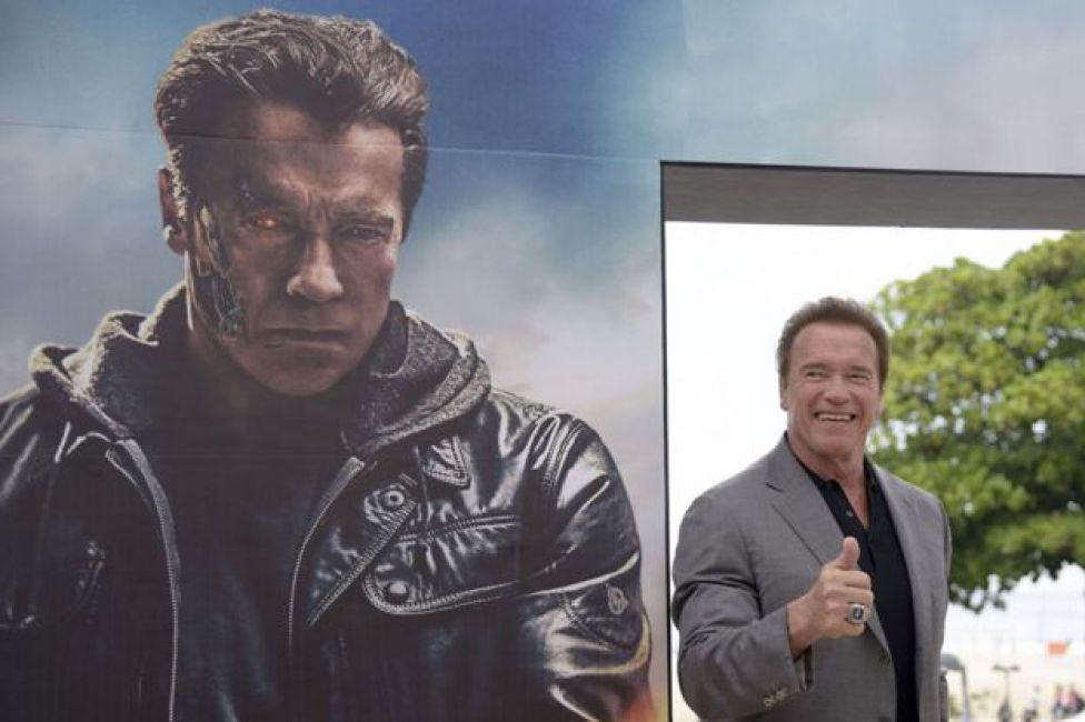 Arnold Schwarzenegger next to a Terminator Genisys hoarding