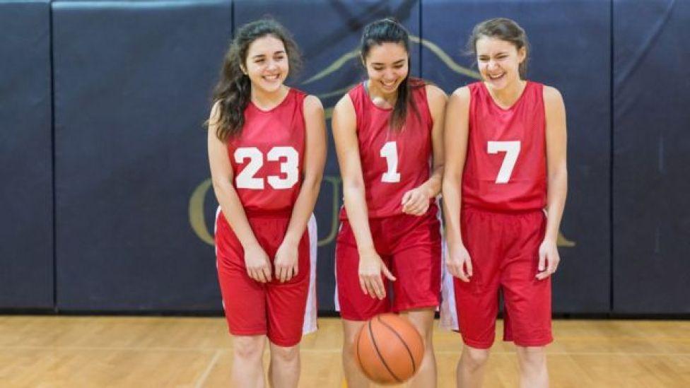 Tres adolescentes miembros del mismo equipo de baloncesto.  Qué tipo de deporte es mejor para estar sano según tu edad  105556388 equipo