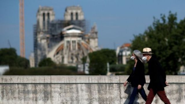 Two people in face masks walk past Notre-Dame in Paris