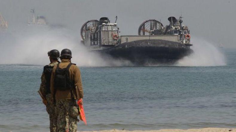 Un aerodeslizante llegando a la costa, donde lo esperan dos soldados