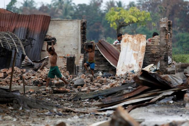 Children recycle goods from the ruins of a market which was set on fire at a Rohingya village outside Maugndaw in Rakhine state, Myanmar, 27 October
