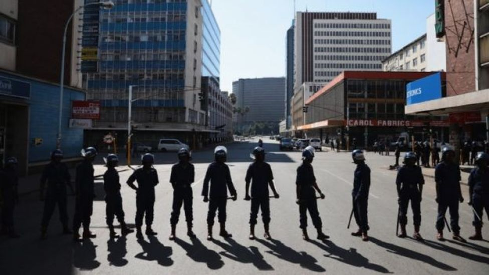 Zimbabwean riot police officers stand guard on an empty street on August 2, 2018 in Harare, Zimbabwe