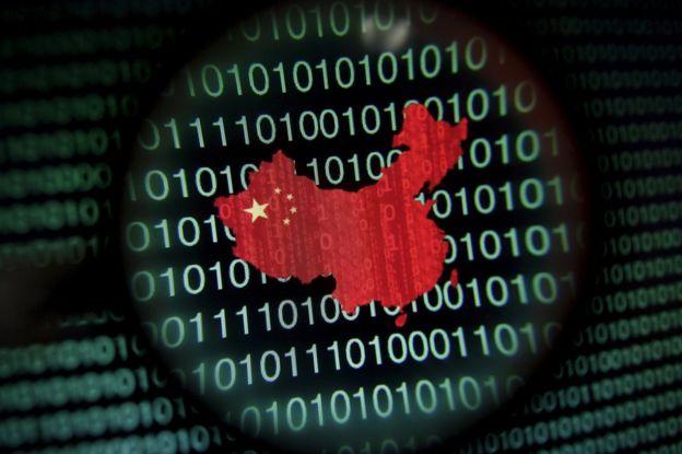 Un mapa de China se ve a través de una lupa en una pantalla de ordenador que muestra los dígitos binarios en This 2 de enero de 2014 foto de archivo ilustración.