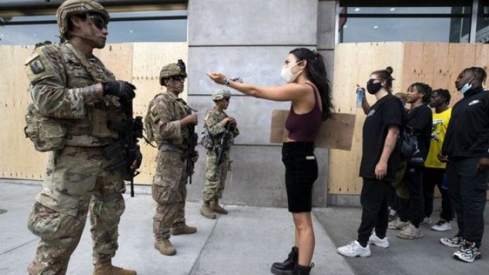 """Demonstrators talk to the National Guard during a march in response to George Floyd""""s death on June 2, 2020 in Los Angeles, California. (GETTY IMAGES)"""