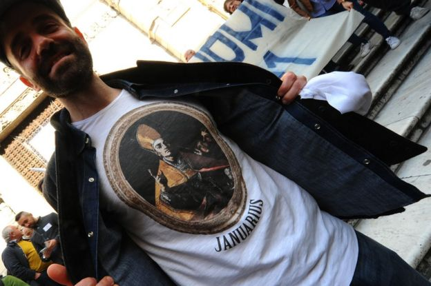 A man shows off his t-shirt depicting San Gennaro outside the cathedral in Naples, 5 March