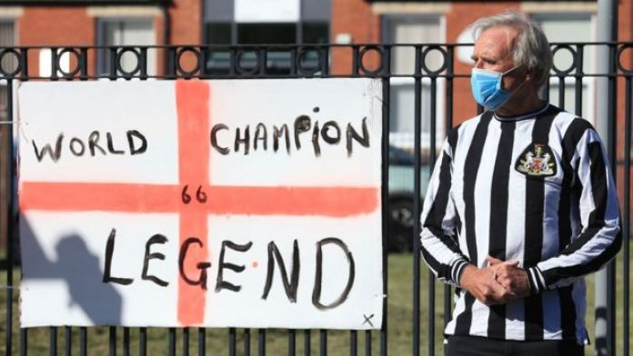 A man in a Newcastle United shirt stands next to a tribute flag celebrating England's 1966 World Cup win
