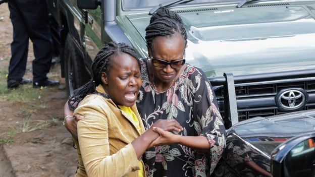Kenyan woman caught up in the attack (L) led away by relative - 16 January