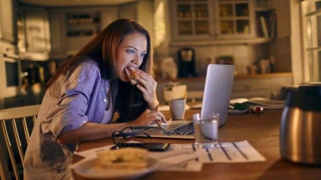 Mulher comendo na frente do computador