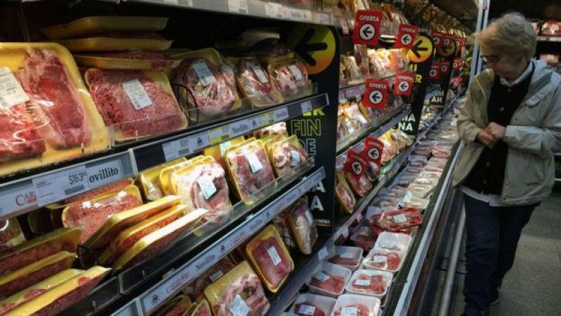 Consumidora olha gôndola de carnes no supermercado