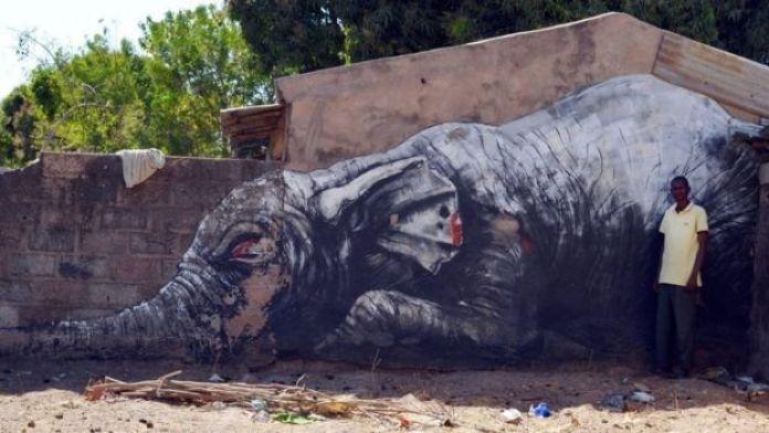 Un homme pose devant une fresque monumentale