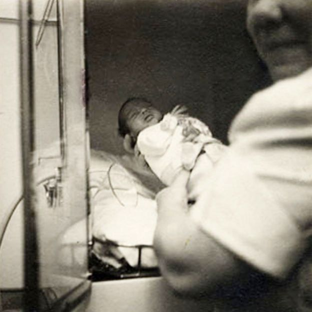 A baby being placed into one of Dr Couney's incubators