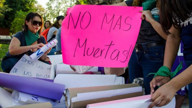 "Women in a protest with a sign that says ""No more dead""."