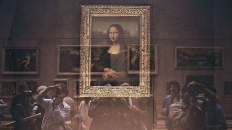 The Mona Lisa behind its bullet-proof glass protection with Japanese tourists at the Louvre Museum