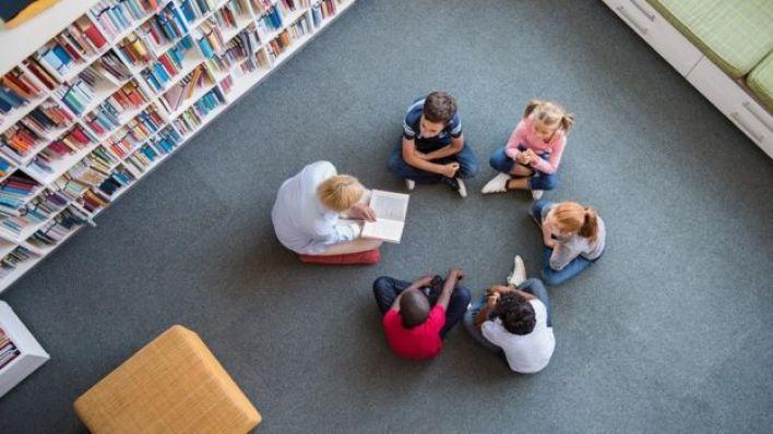 معلم يقرأ قصة على مجموعة من الأطفال