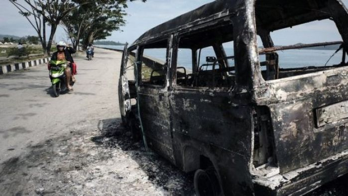 A burnt out car on the West Papuan coastline